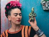 Frida holding an Olmeca figurine at her home, La Casa Azul, in 1939.